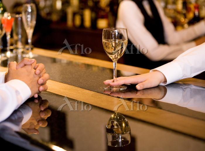 ワインを差し出すバーテンダーと男性の手元