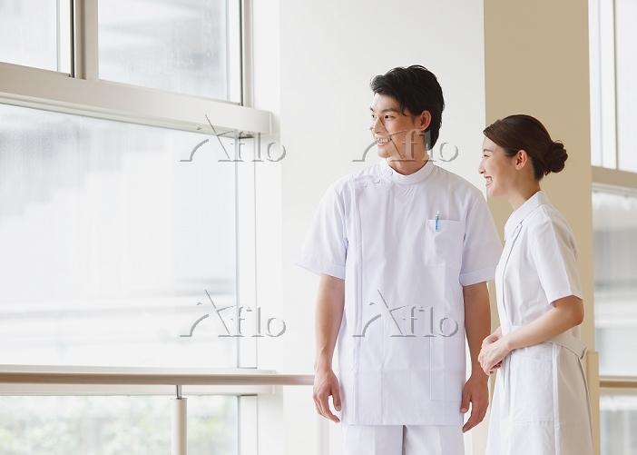 廊下で会話する笑顔の若い看護師