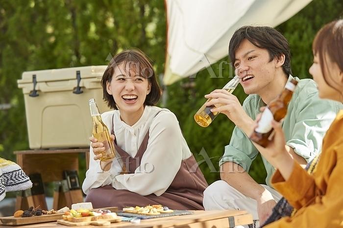 庭でビールを楽しむ日本人若者たち