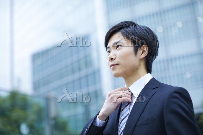 ネクタイを整える日本のビジネスマン