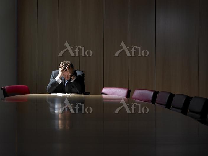 会議室で頭を抱えるビジネスマン