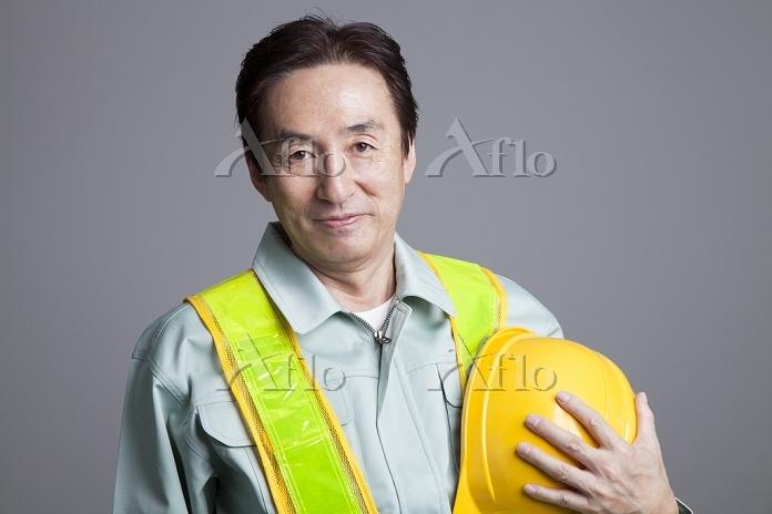 ヘルメットを脱いで微笑む作業員