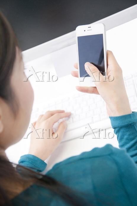 スマートフォンを触るビジネス女性の後姿