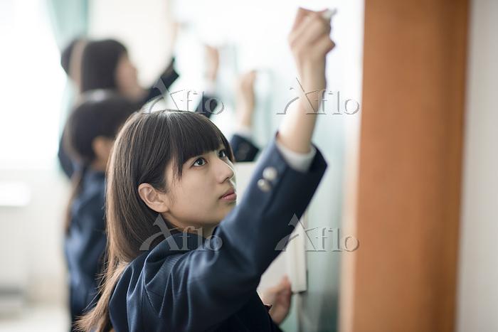 チョークで黒板に答えを書く女子学生