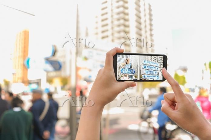 東京の街中でスマートフォンをかざす