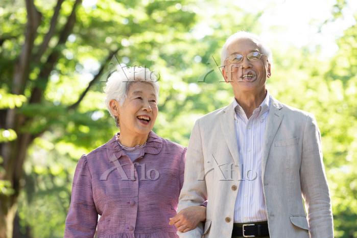寄り添って歩く日本人シニア夫婦