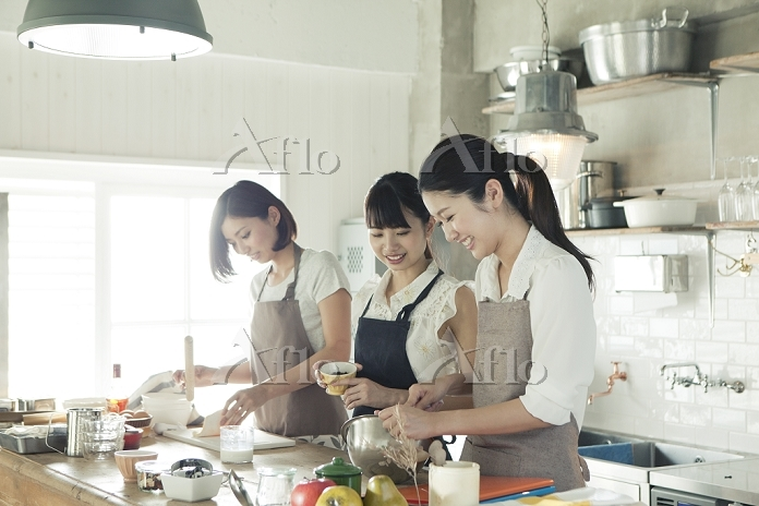 友人とお菓子を作る若い日本人女性