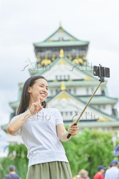 大阪城で自撮りをする日本人女性