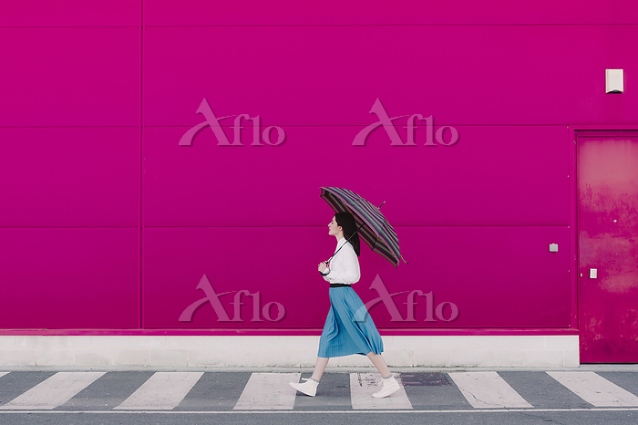 Young woman with umbrella walk・・・