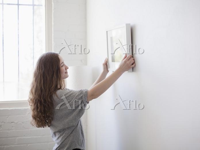 壁に額を飾る女性