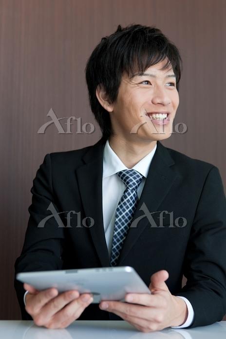 iPadを持っている笑顔のビジネスマン