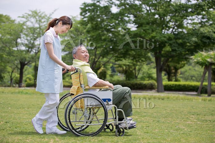 公園で話をするシニア男性と介護士
