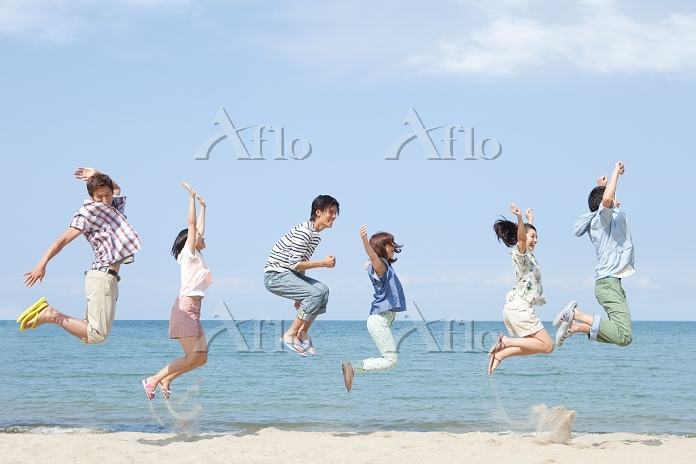砂浜でジャンプをする男女