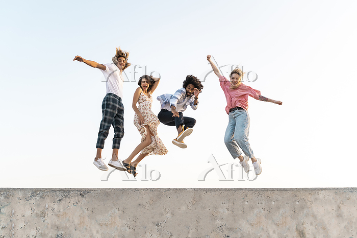 Carefree friends jumping on a ・・・