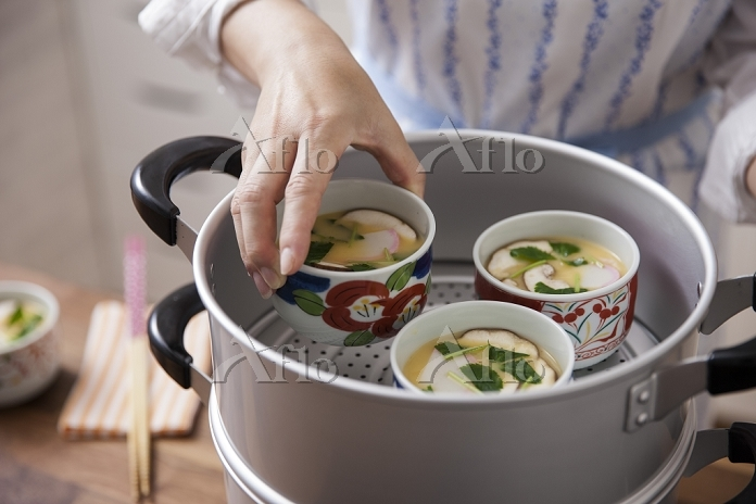 茶碗蒸しを蒸し器に並べる女性