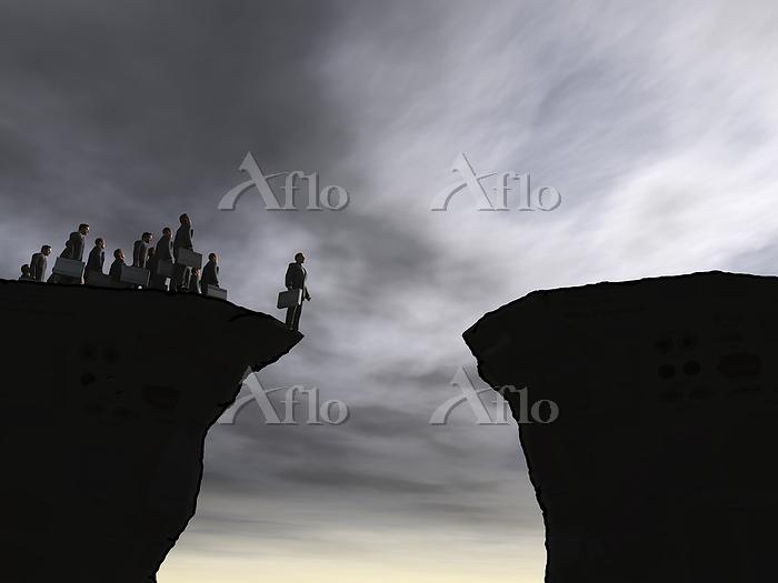 崖の先端に立つビジネスマンその他大勢