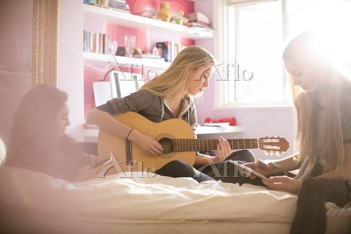 ベッドでギターを弾く女性