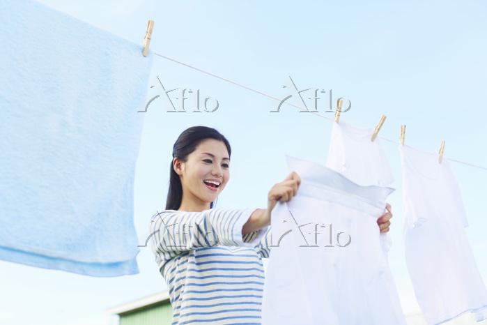 青空のもと洗濯物を干す日本人女性
