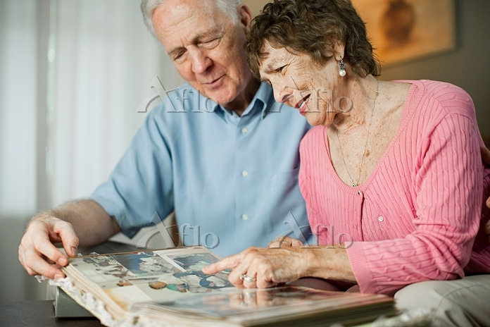 Senior couple looking at famil・・・