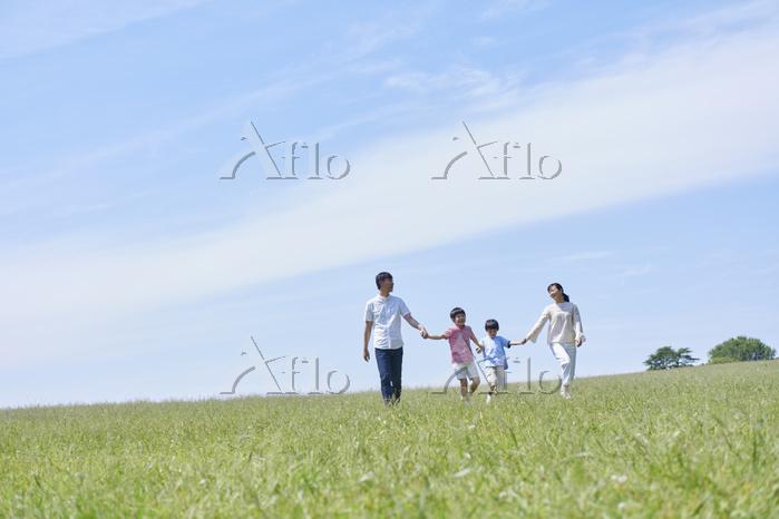 新緑と手を繋いで歩く日本人家族