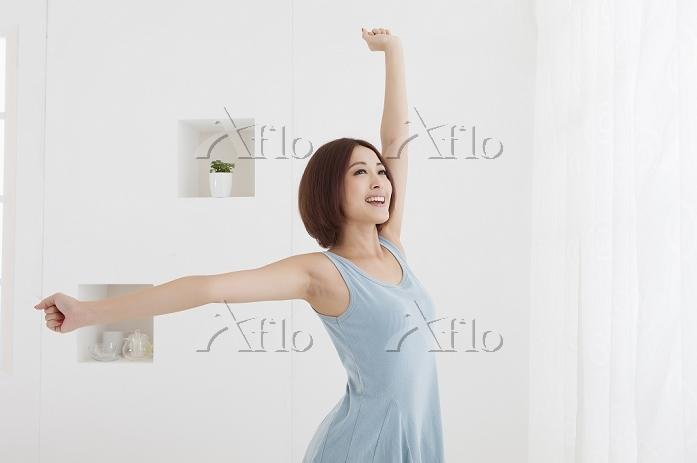 伸びをする若い女性