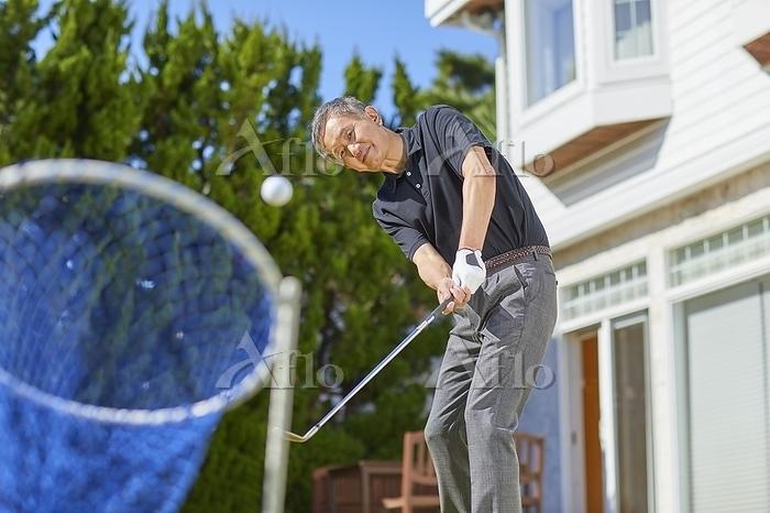 庭でゴルフ練習をする日本人シニア男性