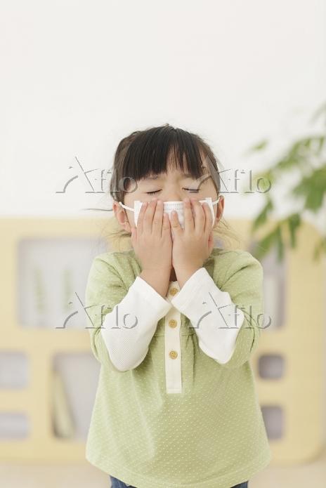 マスクをしてくしゃみをする女の子