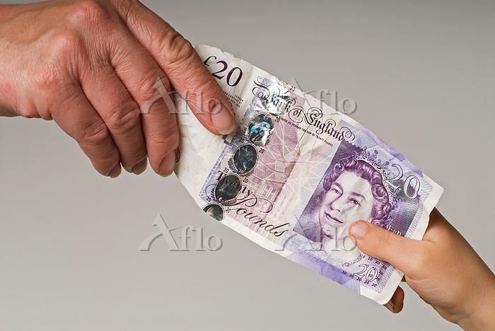 子供に20ポンドを渡す親の手
