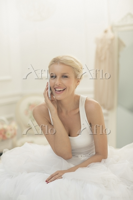Smiling bride talking on cell ・・・