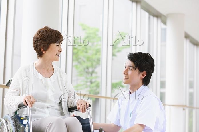車椅子のシニア女性と日本人看護師