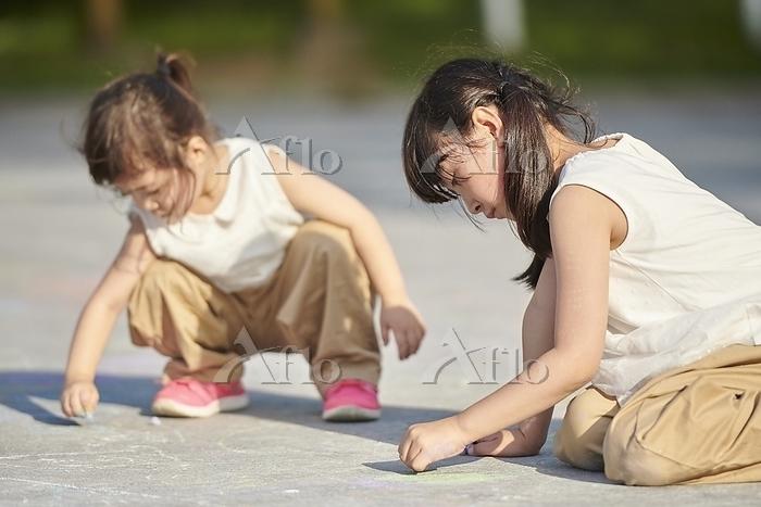 地面にお絵かきをする日本人の女の子