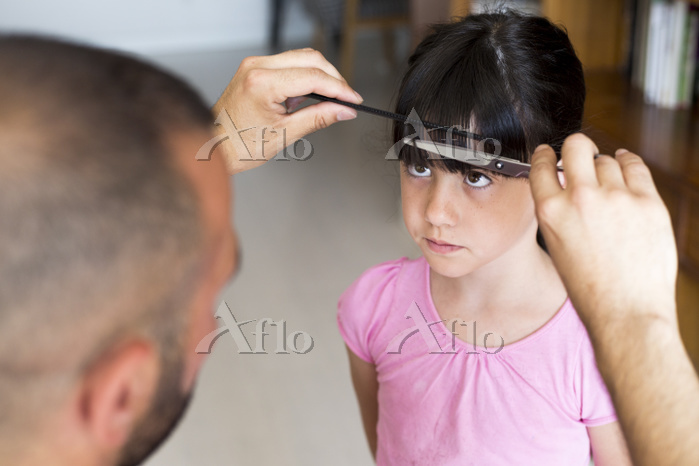Father cutting daughter's hair・・・