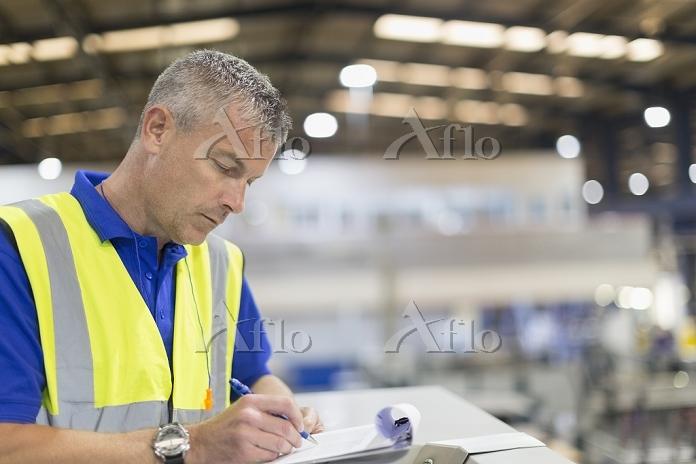 Supervisor writing on clipboar・・・