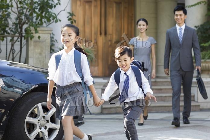 手を繋いで学校へ行く子供たち