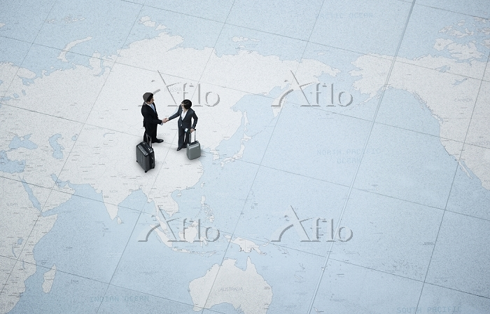 世界地図の上で握手を交わすビジネスマンたち