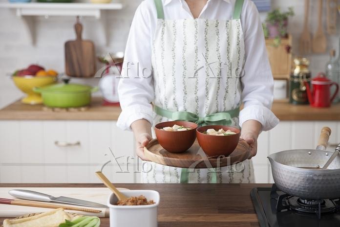 味噌汁の椀を盆に載せて持つ女性
