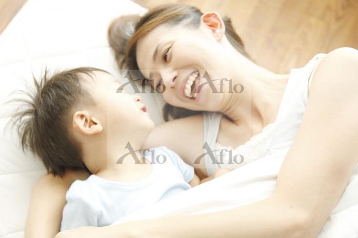 寝そべってスキンシップをとる母と子