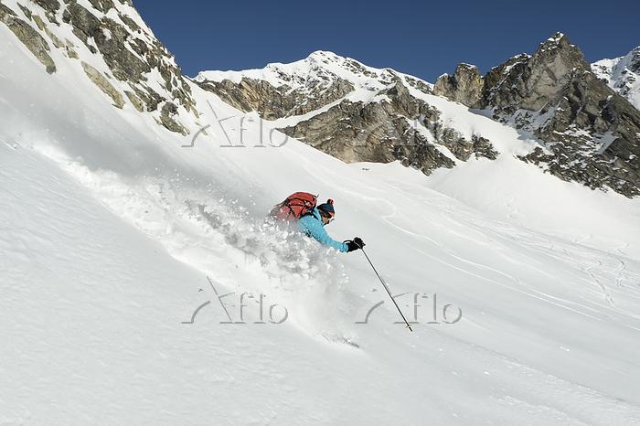 新雪を滑る女性スキーヤー