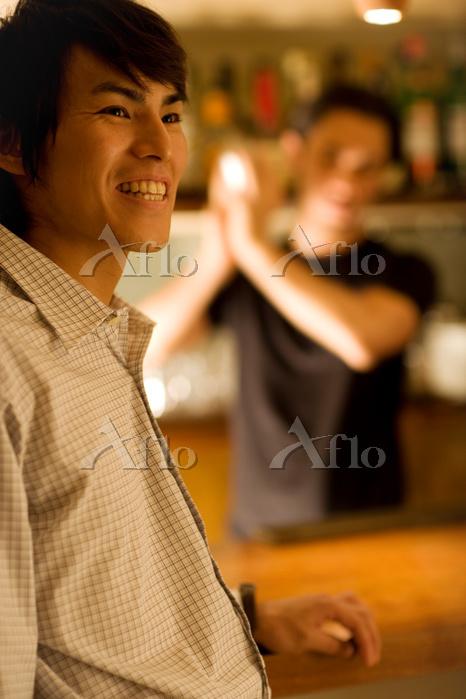 笑顔の男性とシェーカーを振るバーテンダー