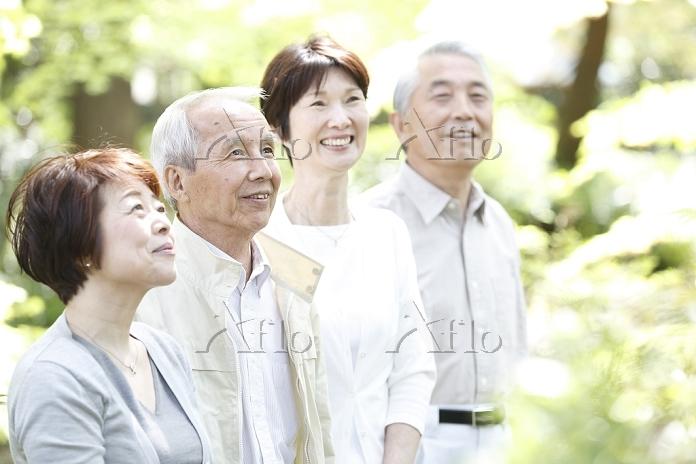 笑顔で新緑を見上げる2組のシニア夫婦