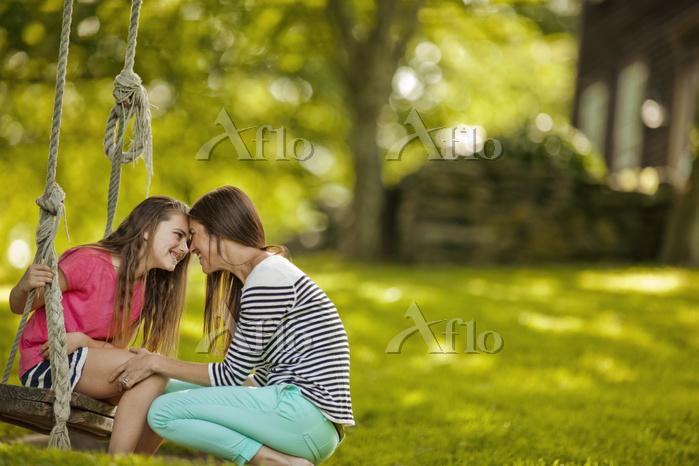 ブランコを乗る女の子と母