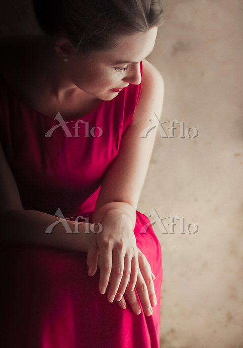 WOMAN IN PINK DRESS SITTING AN・・・