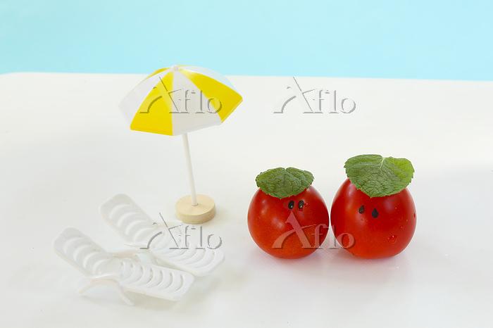 ハーブの葉を乗せた可愛いミニトマトとビーチパラソル