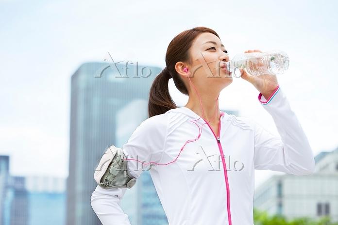 ランニングウェアで水を飲む女性