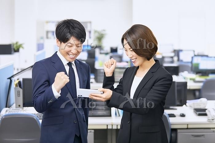 オフィスで観戦するビジネスマンとビジネスウーマン