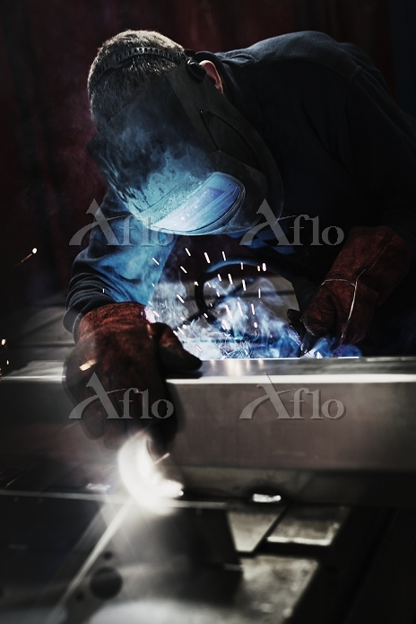 Welder using welding torch in ・・・
