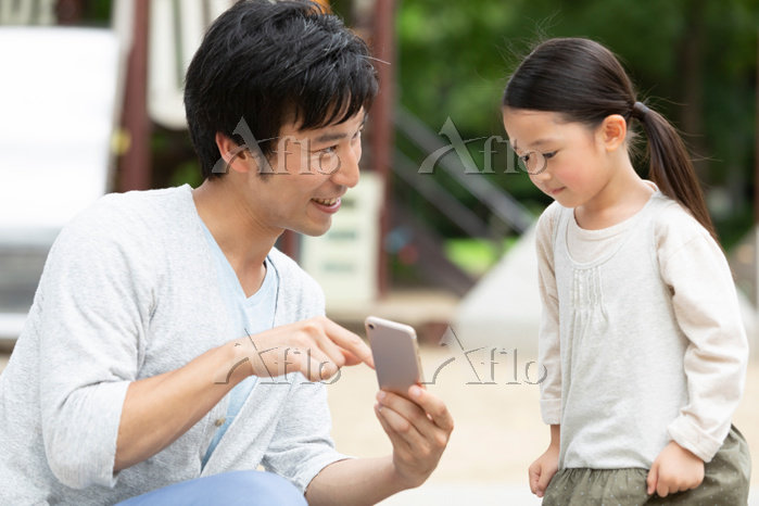 スマートフォンを見せる男性
