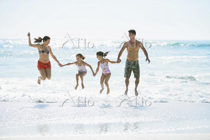 ビーチを歩く外国人家族