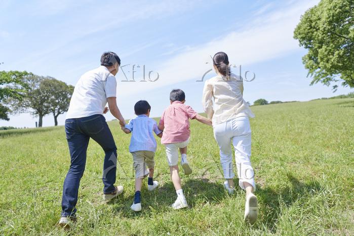 新緑と手を繋いで走る日本人家族