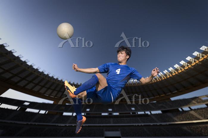 ボレーシュートを打つサッカー選手